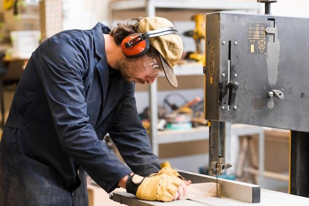 Zijaanzicht van een mannelijke timmerman die meting op werkbank neemt Gratis Foto