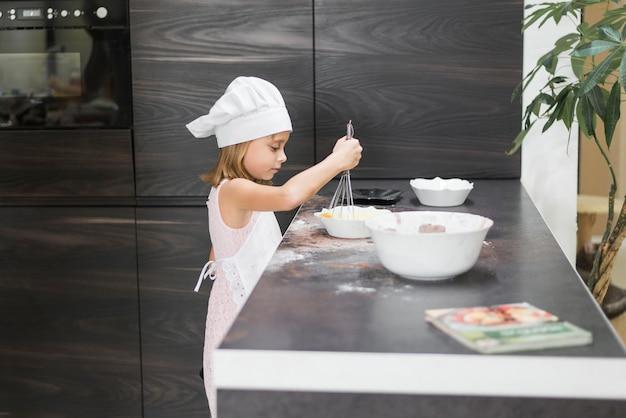 Zijaanzicht van een meisje dat mengsel samen in kom op keuken worktop zwaait Gratis Foto