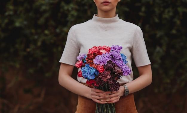 Zijaanzicht van een meisje met een multi-clored boeket van anjerbloemen op donkere muur Gratis Foto