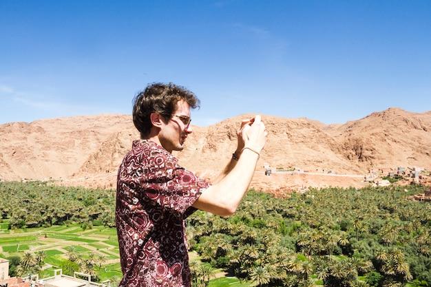 Zijaanzicht van een mens die beeld van oase neemt Gratis Foto