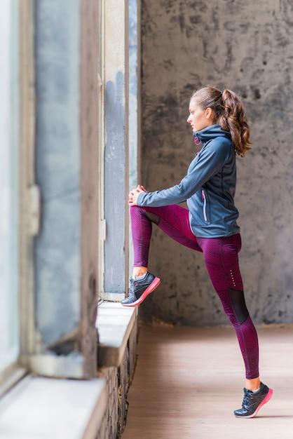 Zijaanzicht van een sportieve jonge vrouw die door venster kijkt Gratis Foto