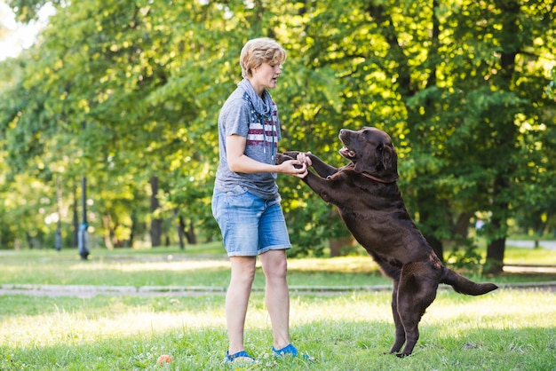 Zijaanzicht van een volwassen vrouw die met haar hond in park speelt Gratis Foto