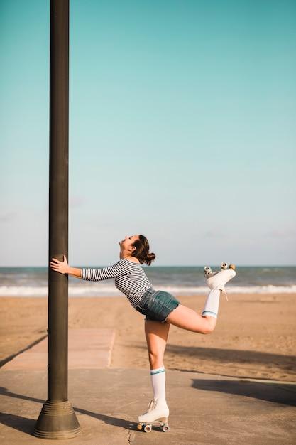 Zijaanzicht van een vrouwelijke pijler van de schaatserholding die zich voor strand bevindt Gratis Foto