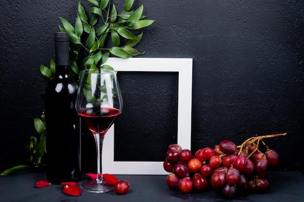 Zijaanzicht van fles en glas rode wijn met druivenkader en bladeren met bloembloemblaadjes op zwarte met exemplaarruimte Gratis Foto