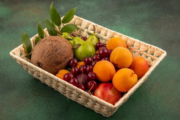 Zijaanzicht van fruit als de kers van de de abrikozenpeer van de kokosnootperzik met bladeren in mand op groene achtergrond Gratis Foto