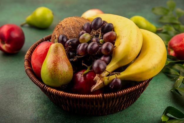 Zijaanzicht van fruit als de perzik van de de druifpeer van de kokosbanaan in mand met bladeren op groene achtergrond Gratis Foto