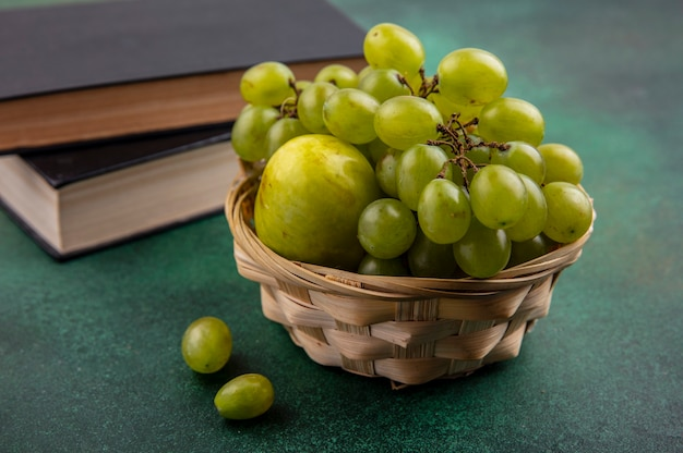 Zijaanzicht van fruit als druif en pluot in mand met gesloten boeken op groene achtergrond Gratis Foto