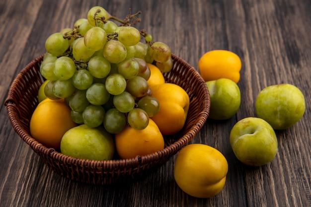 Zijaanzicht van fruit als druif groene pluot en nectacots in mand en patroon van pluots en nectacots op houten achtergrond Gratis Foto