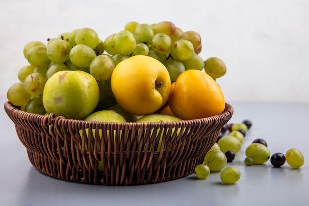 Zijaanzicht van fruit als druif nectacots groene plukken in mand met druiven bessen op grijze ondergrond en witte achtergrond Gratis Foto