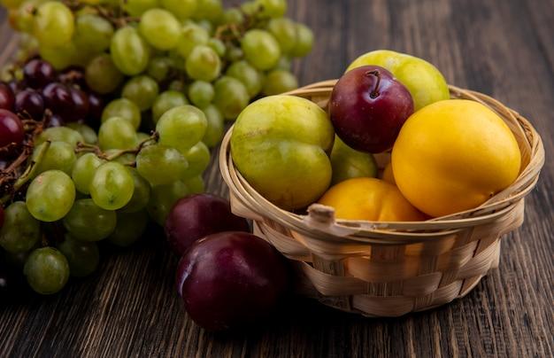 Zijaanzicht van fruit als groene nectacots en smaak koning pluots in mand met druiven op houten achtergrond Gratis Foto