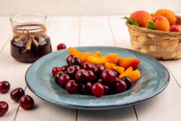 Zijaanzicht van fruit als kersen en abrikozenplakken in plaat en mand van abrikozen met aardbeienjam op houten achtergrond Gratis Foto