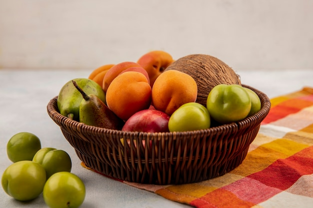 Zijaanzicht van fruit als kokosnoot abrikoos perzik peer in mand op geruite doek met pruimen op witte achtergrond Gratis Foto