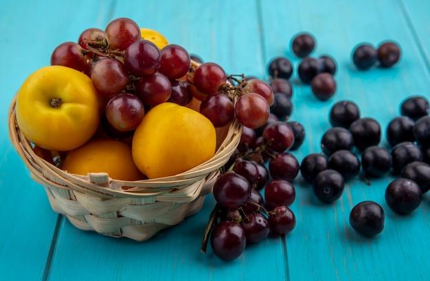 Zijaanzicht van fruit als nectacots en druivenmost in mand en op blauwe achtergrond Gratis Foto