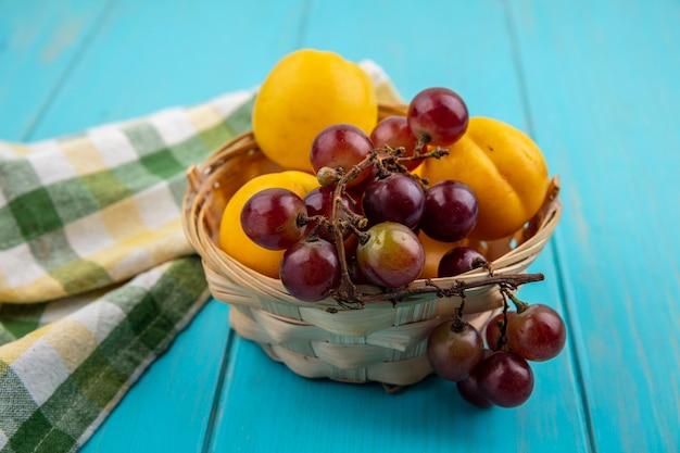 Zijaanzicht van fruit als nectacots en druivenmost in mand met geruite doek op blauwe achtergrond Gratis Foto