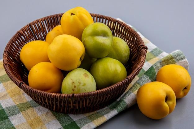 Zijaanzicht van fruit als nectacots groene pluots in mand en op geruite doek op grijze achtergrond Gratis Foto