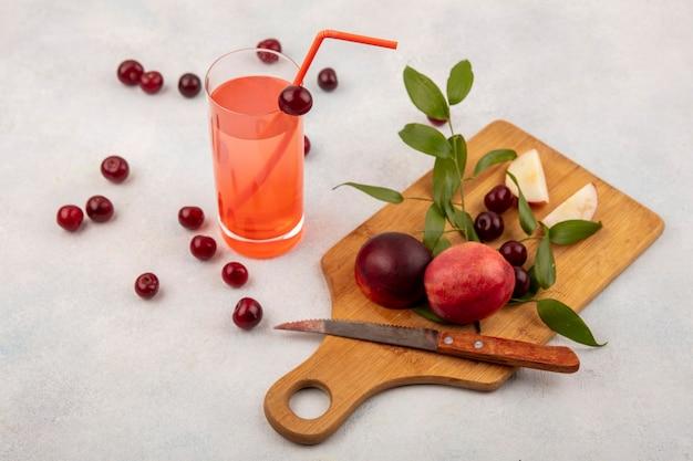 Zijaanzicht van fruit als perzik en kers met mes op snijplank en kersensap op witte achtergrond Gratis Foto