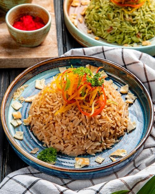 Zijaanzicht van gebakken japanse rijst met groenten in sojasaus op een plaat op hout Gratis Foto