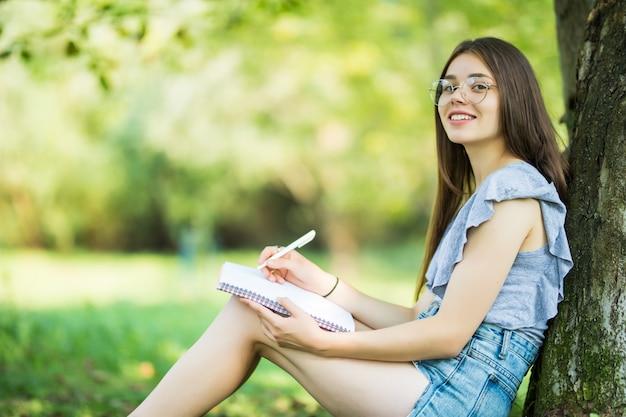 Zijaanzicht van geconcentreerde brunette vrouw in bril zitten in de buurt van de boom in het park en iets op laptop schrijven Gratis Foto