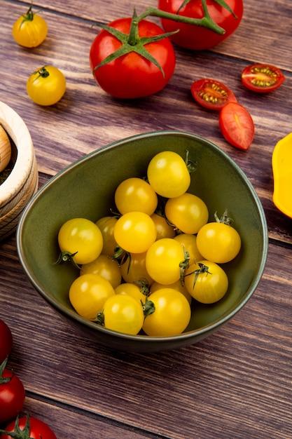 Zijaanzicht van gele tomaten in kom met rode op hout Gratis Foto