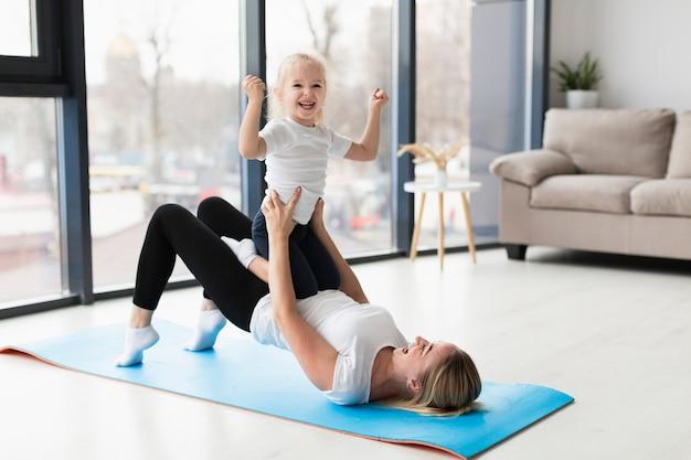 Zijaanzicht van gelukkige moeder en kind thuis oefenen Gratis Foto