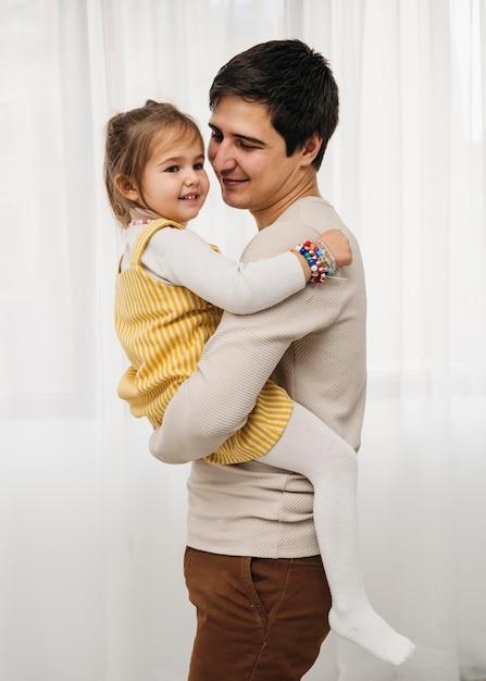 Zijaanzicht van gelukkige vader die zijn dochter houdt Gratis Foto