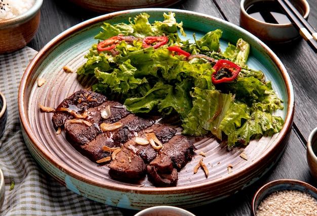 Zijaanzicht van geroosterd rundvlees met sla en rode spaanse peperpeper op een plaat op hout Gratis Foto
