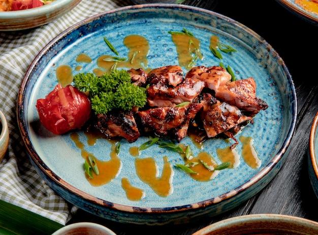 Zijaanzicht van geroosterde kip met gegrilde tomaten verse kruiden en saus op een plaat op hout Gratis Foto