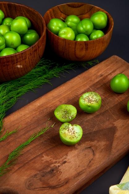 Zijaanzicht van gesneden groene pruimen besprenkeld met gedroogde pepermunt op een houten snijplank en houten kommen gevuld met groene pruimen op zwarte tafel Gratis Foto