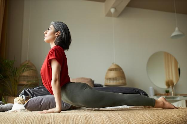 Zijaanzicht van gespierde jonge grijze harige vrouw beoefenen van yoga in de slaapkamer, opwaarts gerichte hond pose doen Gratis Foto