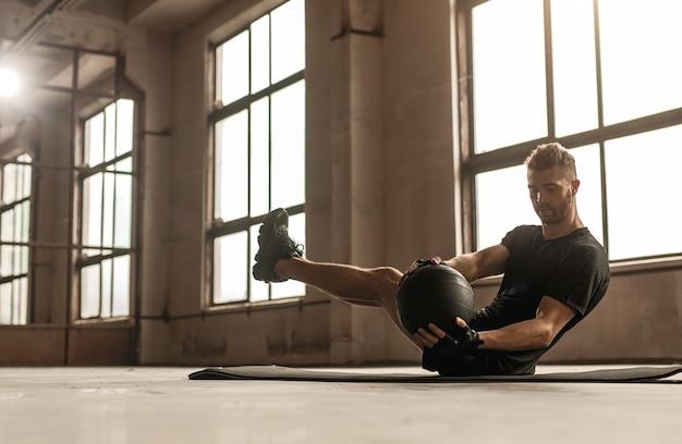 Zijaanzicht van gespierde mannelijke atleet abs oefening met bal tijdens intensieve fitnesstraining in de sportschool doet Premium Foto