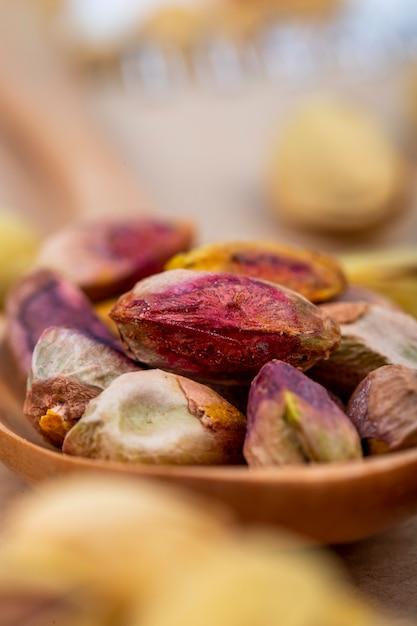 Zijaanzicht van gezouten geroosterde pistachenoten op houten lepel Gratis Foto