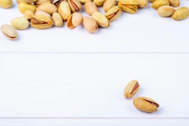 Zijaanzicht van gezouten geroosterde pistachenoten op witte achtergrond met exemplaarruimte Gratis Foto