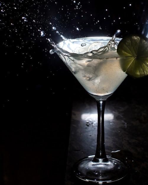 Zijaanzicht van glas martini en splash van vallende ijs op zwart Gratis Foto