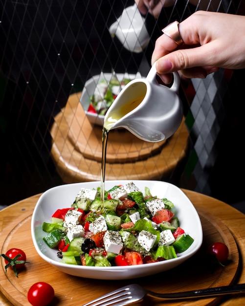 Zijaanzicht van hand gietende olijfolie op verse salade met feta-de tomatenkomkommers van de kaas in witte kom Gratis Foto