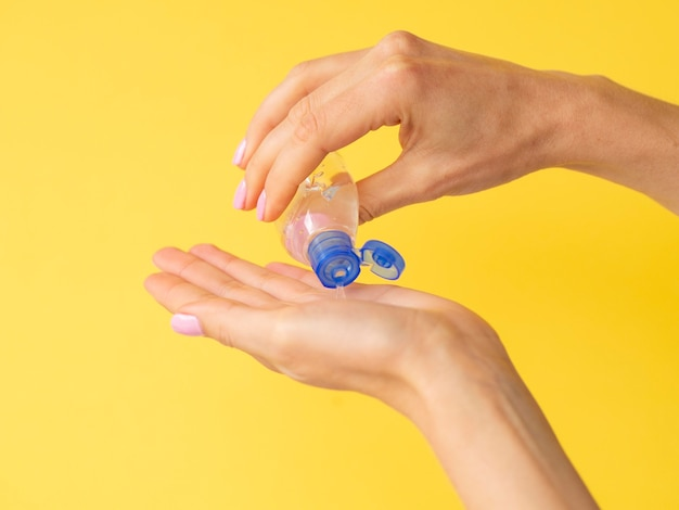 Zijaanzicht van handen die handdesinfecterend middel gebruiken Premium Foto