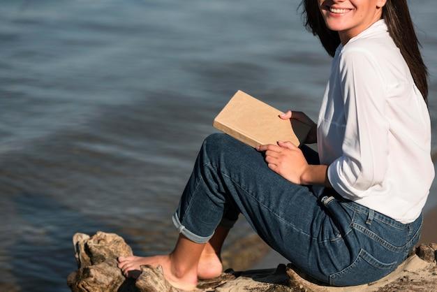 Zijaanzicht van het boek van de vrouwenholding bij het strand Gratis Foto
