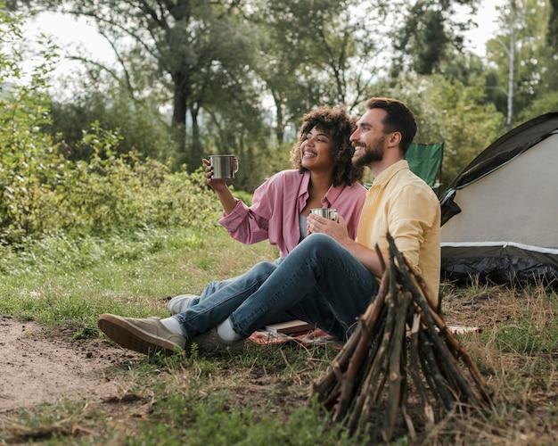 Zijaanzicht van het paar dat van het uitzicht geniet tijdens het kamperen Gratis Foto