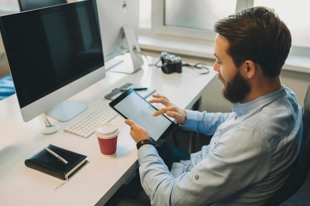Zijaanzicht van het zitten op kantoor werkplek met computer, camera en papier beker ongeschoren mannelijke scrollen scherm van tablet in handen Premium Foto