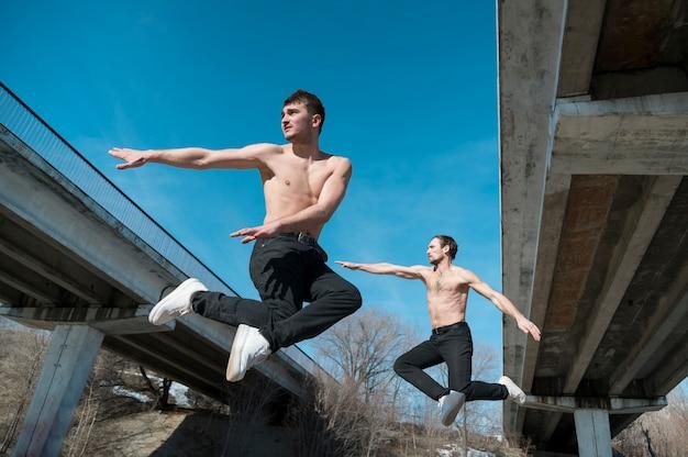 Zijaanzicht van hiphopdansers die mid-air stellen Gratis Foto