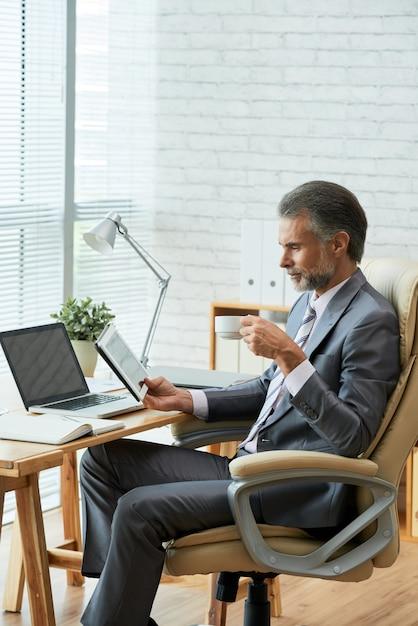 Zijaanzicht van hogere directeur die digitale tablettouchscreen bekijken terwijl het nippen van koffie Gratis Foto