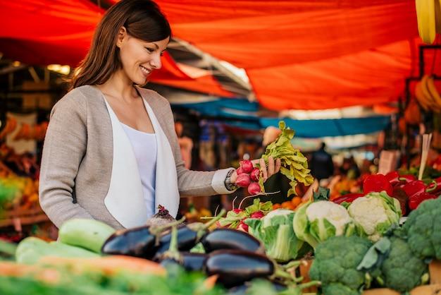 Zijaanzicht van jonge vrouw bij landbouwersmarkt, die groenten kiest. Premium Foto