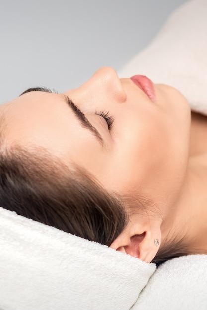 Zijaanzicht van jonge vrouw liggend op de tafel van de schoonheidsspecialiste met gesloten ogen tijdens het wachten op cosmetische procedure in de schoonheidssalon Premium Foto