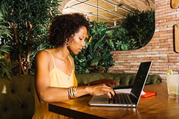 Zijaanzicht van jonge vrouw met behulp van laptop op houten tafel in het restaurant Gratis Foto