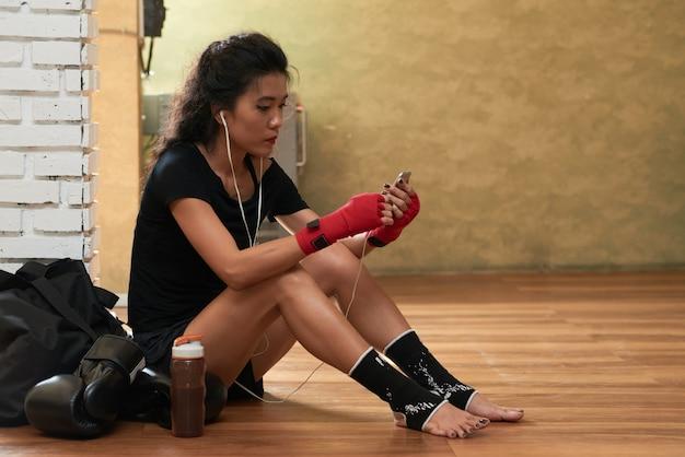Zijaanzicht van jonge vrouwelijke atleet die aan muziek na de training luistert Gratis Foto