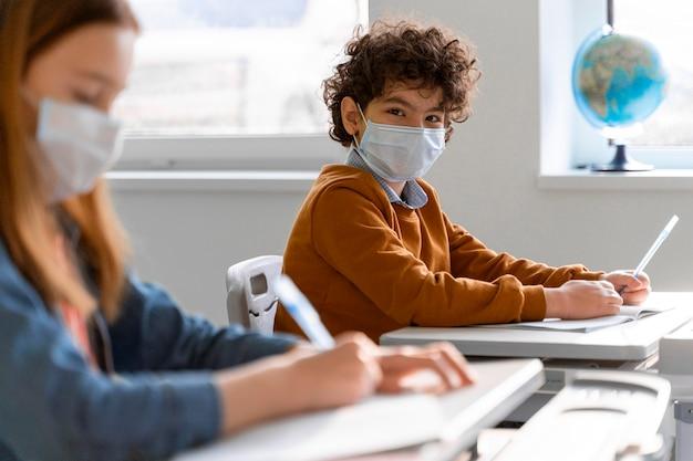 Zijaanzicht van kinderen met medische maskers in het leren van de klas Gratis Foto