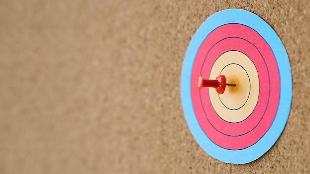 Zijaanzicht van kleurrijk doel met speld op schot in de roos Gratis Foto