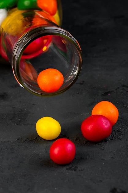 Zijaanzicht van kleurrijk suikergoed dat van glasfles wordt verspreid op zwarte Gratis Foto