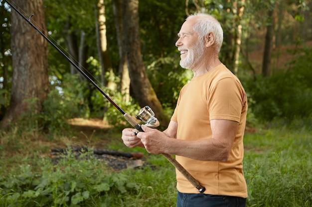 Zijaanzicht van knappe europese mannelijke gepensioneerde m / v vangen van vis tegen pijnbomen, staaf met vangst uit water trekken, gelukkig glimlachen, genieten van actieve outdoor hobby in de wilde natuur Gratis Foto