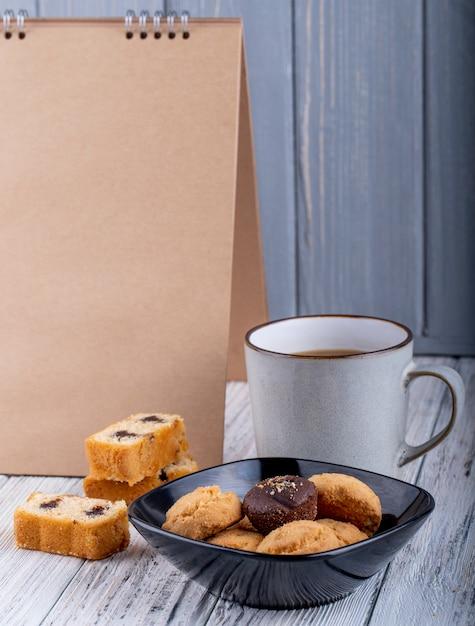 Zijaanzicht van koekjes in een zwarte kom en een kop met cacao op houten Gratis Foto