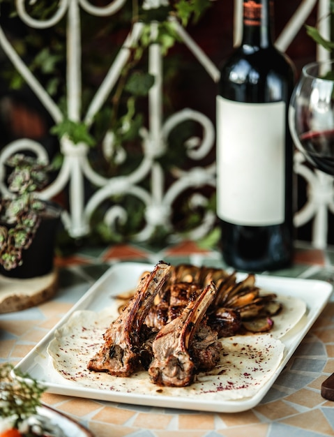 Zijaanzicht van lam rib kebab met gebakken aardappelen op tafel met een fles rode wijn Gratis Foto